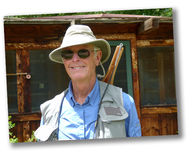 Dee Hubbard wearing sunglasses and fishing out standing in front of a cabin
