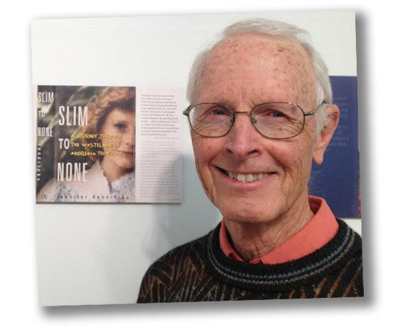 Dee Hubbard standing in front of a copy of his book, Slim to None