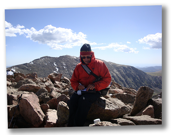 Dee Hubbard signing the vista registry at the top of a Colorado 14er